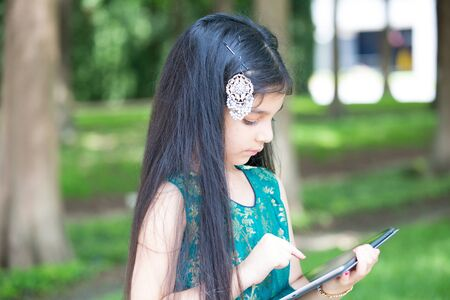 Closeup portrait, young girl typing on digital tablet, isolated outside outdoors background Stock Photo