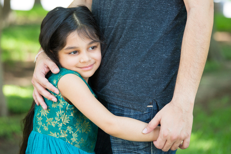 hispanic girl: Closeup portrait, young child hugging her father tenderly, isolated outdoors outside green grass background. Daddys little girl Stock Photo