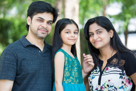 Closeup portrait, adorable family posing outdoors, isolated green trees outside outdoors background