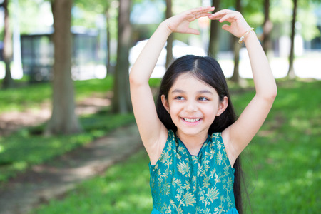 Closeup portrait, young girl posing as ballet dancer, hands up, isolated outside outdoors background