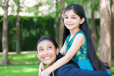 Closeup portrait, family having fun hanging out, girl sitting on top woman shoulders, isolated green trees outdoors background Stock Photo