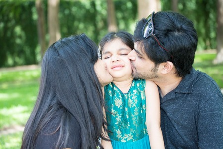 liking: Closeup portrait, young girl being kissed my parents and not liking it, isolated outdoors outside background