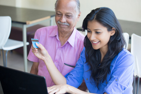 Closeup portrait rich elderly gentleman in pink shirt and lady in blue top holding credit card doing online shopping. Booming economy concept, buy, sell, award. Make money at home