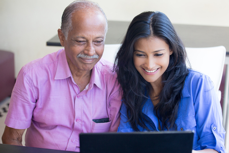 Closeup portrait, sitting young woman showing elderly man to use black laptop, happy at what they see , isolated indoors background