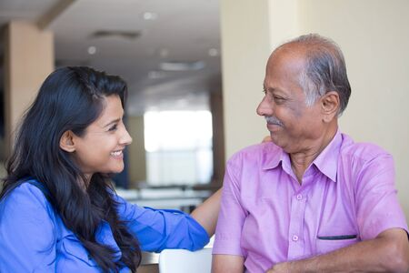 Closeup portrait, family, young woman in blue shirt affectionately gazing older man in pink collar button , happy isolated indoors home background