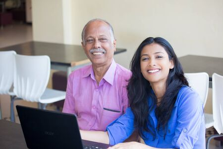 Closeup portrait, sitting young woman showing elderly man to use black laptop, smiling pose , isolated indoors background photo