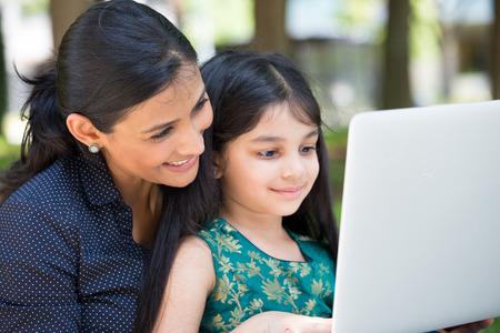 Close-upportret, familie die zilveren laptop samen bekijken, geïsoleerde in openlucht buiten achtergrond