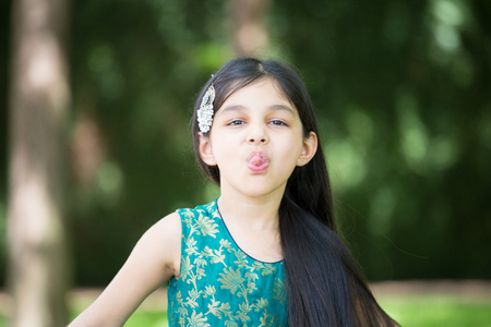 scamp: Closeup portrait, young girl sticking tongue out making funny faces, isolated outside outdoors background