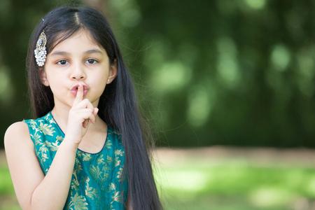 Close-upportret, jong meisje die vinger plaatsen op mond die shh, geïsoleerde buiten in openlucht achtergrond zeggen