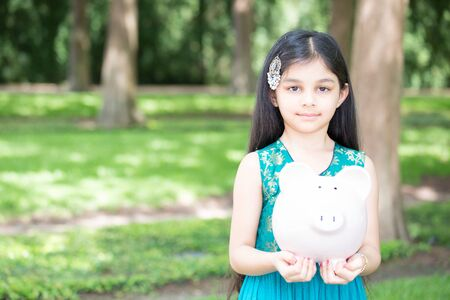 Closeup portrait, young lady holding piggy bank, isolated outdoors green grass and trees background. Money building strategy