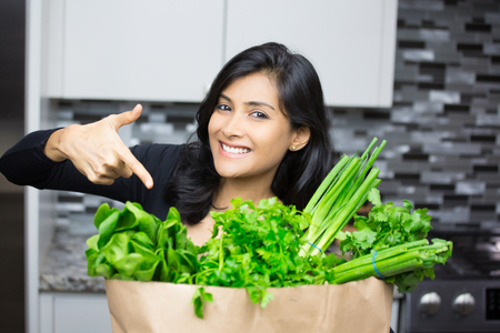 sourced: Closeup portrait, young woman pointing to bag full of green groceries, healthy nutritious balanced diet, isolated indoors home background. Locally sourced food