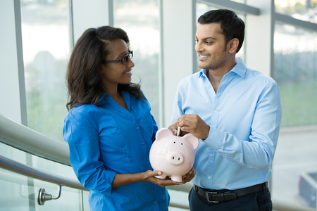 business decisions: Closeup portrait, two smart professionals in blue shirts holding piggy bank, isolated office indoors background. Powerful financial and banking business solutions, decisions concept