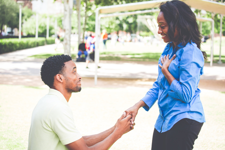 Portrait of young man dropping on knees to propose and lady answering i do, isolated outdoors outside background