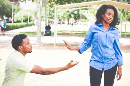 Portrait of young woman showing talk to hand gesture to desperate man hoping to persuade her to see his point. Please take me back. Isolated outdoors outside background