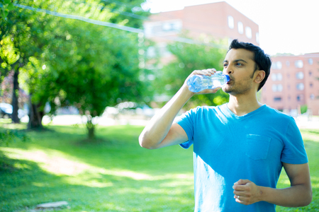 Closeup portrait of young guy in blue shirt drinking water from crystal clear bottle on a hot, sunny day, isolated green trees and building background