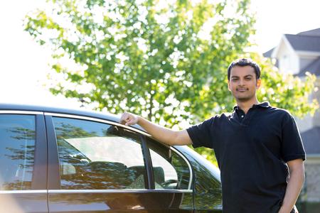 分離のグリーン ツリーの背景色、彼の車で休んで黒のポロシャツで若い男のポートレート、クローズ アップ
