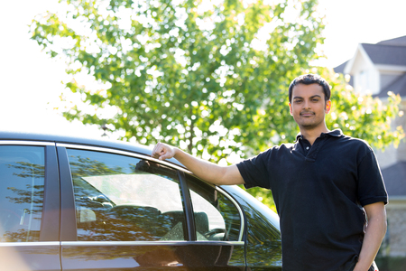 Closeup portrait of young guy in black polo shirt resting on his car, isolated green tree background Stock fotó