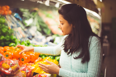 Closeup portrait, young woman in green sweater picking bell peppers with lots of options at grocery store, isolated produce background 免版税图像