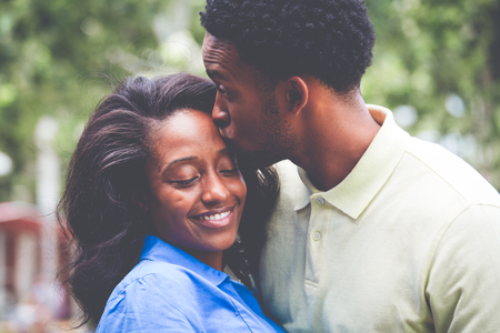 Closeup portrait of a young couple, guy in yellow shirt kissing woman with blue shirt, happy moments, positive human emotions on isolated outdoors outside background. Standard-Bild
