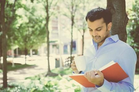 Close-up portret jonge zakenman lezen rode boek en drinken van mok, staan buiten op zonnige dag, geïsoleerde groene bomen achtergrond
