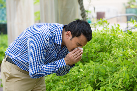 Close-upportret van de jonge mens in blauw overhemd met allergie of koude, blazend zijn neus met een weefsel, kijkend miserabele onwel zeer ziek, geïsoleerde buiten groene bomenachtergrond. Griepseizoen, vaccinatie. Stockfoto
