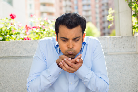 Closeup portrait of guy in blue shirt about to vomit, isolated outdoors outside background
