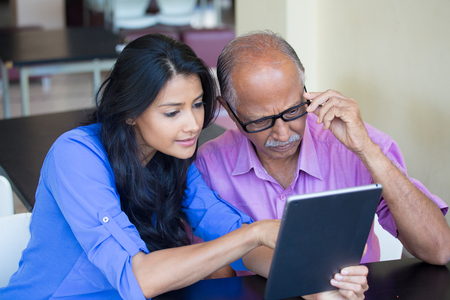 Closeup portrait, sitting young woman showing elderly with black glasses to use portable device,scrutinizing data with great concern, isolated indoors background Stock Photo