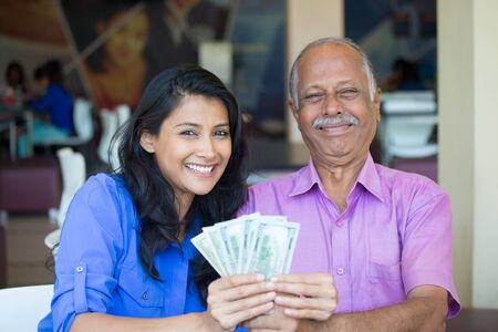 Closeup portrait rich elderly gentleman in pink shirt and lady in blue top holding greenbacks. Booming economy concept, buy, sell, award. Make money at home photo