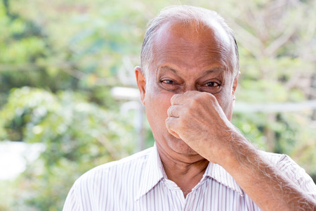 Closeup portrait, senior mature man, disgust face, pinch nose, something stinks, very bad smell, isolated outdoors outside background. Negative emotion, facial expression photo