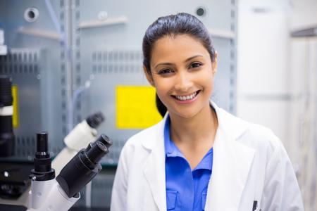 Closeup retrato, joven científico sonriente en bata de laboratorio blanco de pie por microscopio. Laboratorio aislado. Investigación y desarrollo. Foto de archivo