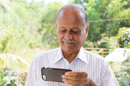 Closeup portrait, elderly gentleman in white striped shirt holding smartphone seeing good news text message, isolated outside outdoors background photo