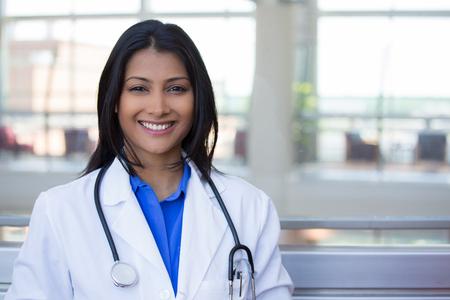 Close-up headshot portret van vriendelijke, vrolijke, lachende zelfverzekerde vrouw, zorgverlener met lab coat. Geïsoleerde binnenkliniek kantoor achtergrond. Patient bezoek.
