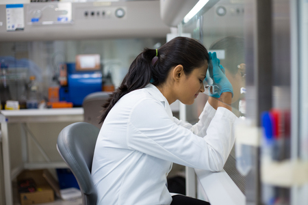 Closeup portrait, tired young woman scientist,crashing, with failed experiments and working long hours, leaning head against glass fume hood with mirror reflection. Isolated laboratory Stock Photo