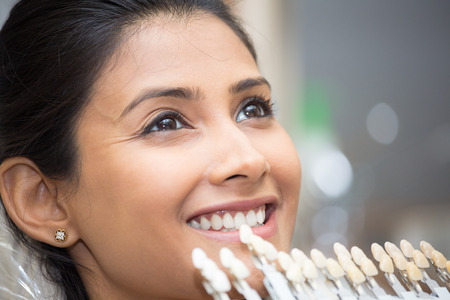 Closeup portrait of young woman getting shade of teeth selected by dental professional for treatment purposes