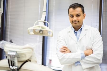 Close-up portret van zelfverzekerde zorgverlener met armen gevouwen staande naast witte patiënt stoel Stockfoto