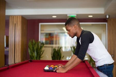 Closeup portrait, young man hanging out, playing billiards at red pool table, isolated indoors background Banco de Imagens