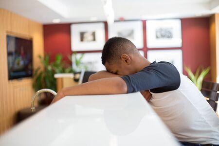 Close-upportret, jonge die mens bij slecht nieuws wordt verstoord, liggend op wit lijsthoofd over wapens, geïsoleerde binnen het leven gebiedsachtergrond