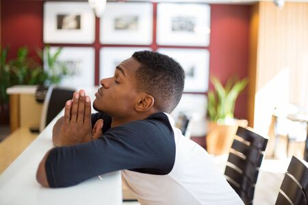 Closeup portrait, young man praying on the white table, hoping for the best ,isolated indoors living area background