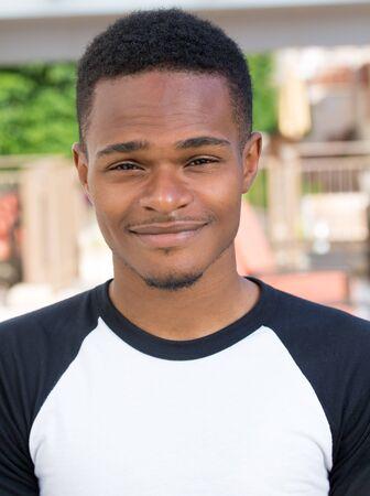 Close-up headshot portret van fijne jonge man, student undergrad, glimlachen, geïsoleerd op buiten buiten achtergrond. Klanttevredenheidsgarantie Stockfoto
