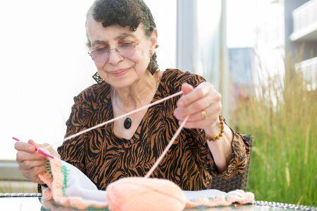 Close-up portret, grootmoeder zitten en haken, geïsoleerde buitenshuis achtergrond