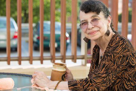 Het profielportret van het close-up zijaanzicht, grootmoeder die kop van drank genieten, isoleerde in openlucht achtergrond Stockfoto