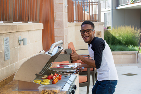 Closeup portrait, handsome young guy with big glasses barbecuing yummy food, isolated outside background