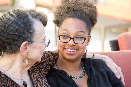 Close-upportret, kleindochter en grootmoederszitting, die diep gesprek hebben, bekijkend elkaar, geïsoleerde in openlucht achtergrond Stockfoto