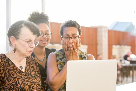 Close-upportret, multigenerationele familie die iets bekijken vreselijk op laptop, geïsoleerde in openlucht achtergrond Stockfoto