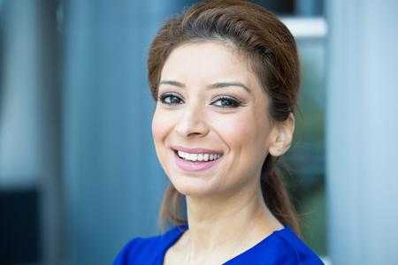Close-up portret, jonge professionele, mooie zelfverzekerde vrouw in blauwe jurk, vriendelijke persoonlijkheid, lachende geïsoleerde binnenkant kantoor achtergrond. Positieve menselijke emoties