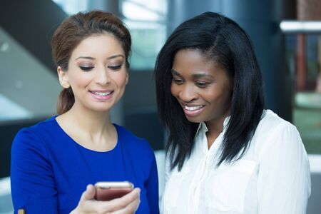 Closeup portrait two women enjoying watching entertainment on phone screen, laughing in humor, isolated indoors inside office background