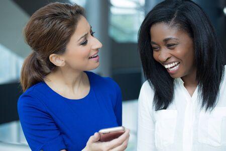 Close-up portret twee vrouwen genieten van entertainment kijken op de telefoon scherm, lachen in humor, geïsoleerde binnen binnen kantoor achtergrond Stockfoto