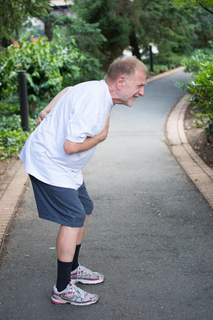Closeup portrait, old man clutching chest, having heart pain, after strenuous workout, isolated outdoors, green trees background. Myocardial infarction, aortic aneurysm rupture