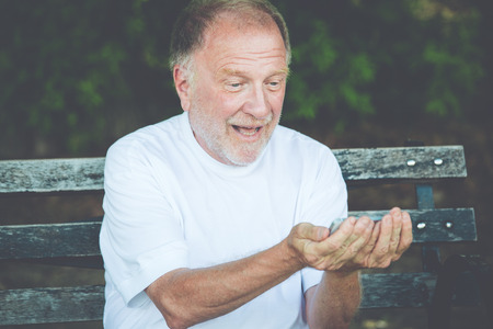 Closeup portrait of bold elderly man in white shirt, excited, checking smartphone, sending text message, seated on a bench, isolated outdoor background.