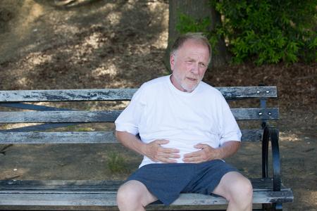 Close-upportret, oude mens clutching maag, die buikpijn hebben, zittend op bank, in openlucht geïsoleerde, groene bomenachtergrond. Vol na een maaltijd of pijn na het lopen Stockfoto